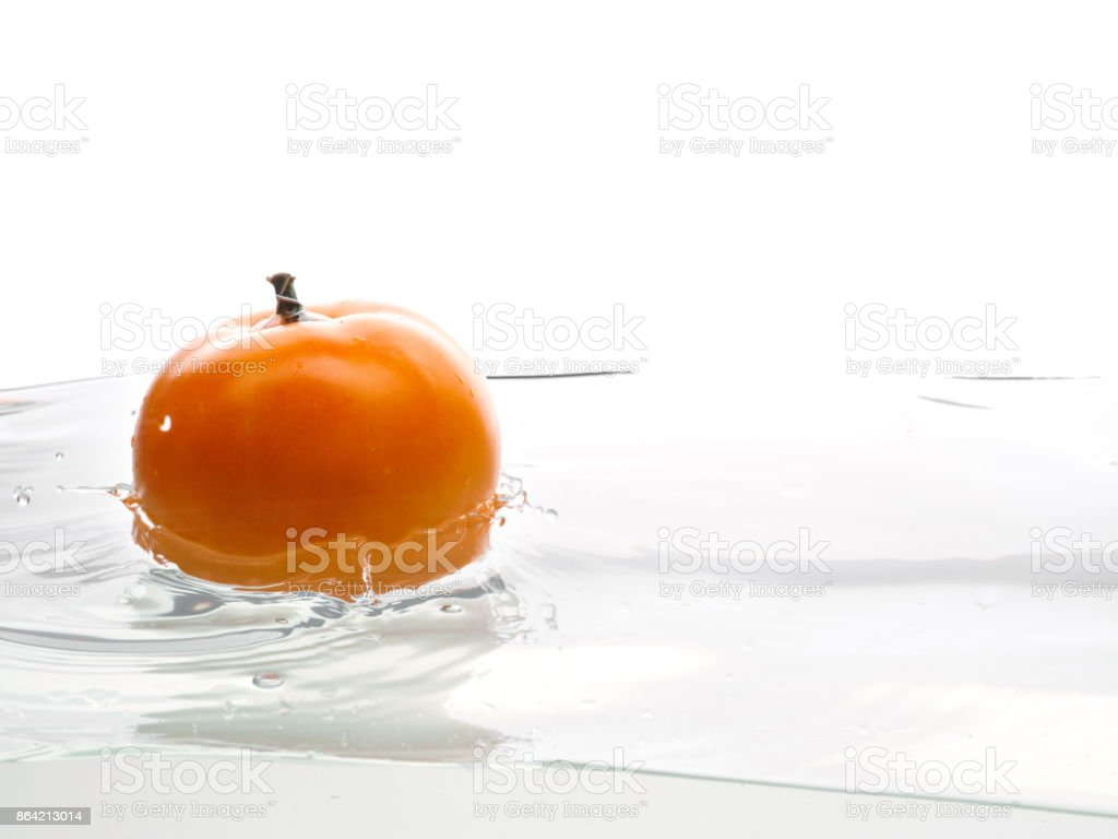 Yellow tomato fall in water. Photo in action. Drops of water. Isolated white background royalty-free stock photo