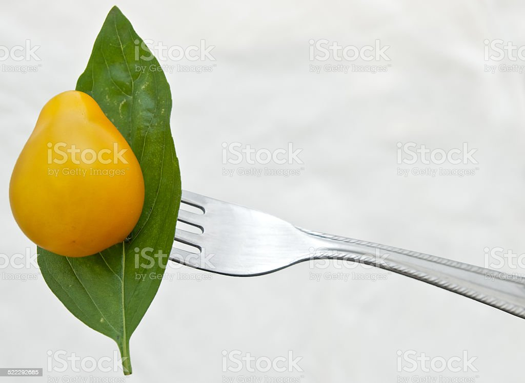 Yellow tomato in a fork stock photo