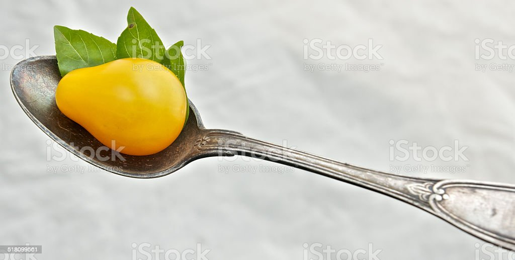 Yellow tomato in a spoon stock photo