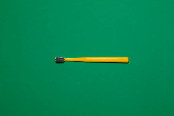 yellow toothbrush on green background stock photo