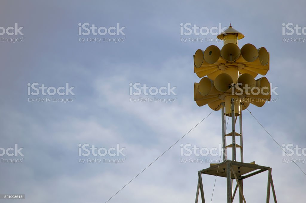 Yellow tornado siren in a sunny sky stock photo