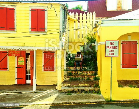 St. Croix, US Virgin Islands-March 11, 2012:  Local man sits between two yellow and red buildings in downtown Christiansted, USVI.