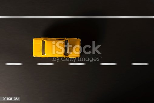 912120622 istock photo Yellow toy car on a black background. 921081384