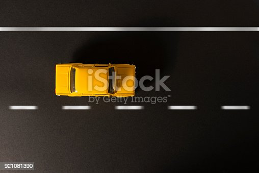912120622 istock photo Yellow toy car on a black background. 921081390