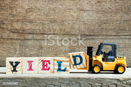 istock Yellow toy forklift hold letter block D to complete word yield on wood background 1013403362