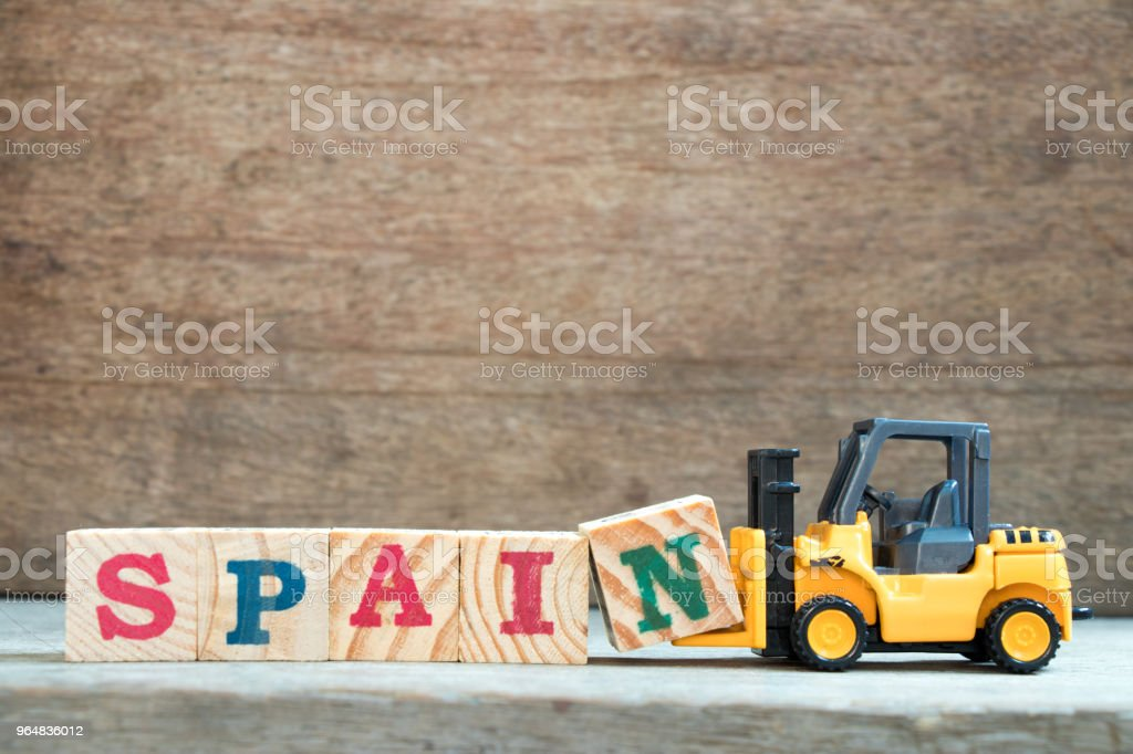 Yellow toy forklift hold letter block N to complete word Spain on wood background royalty-free stock photo