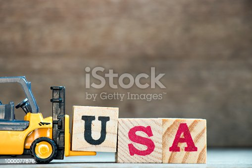 istock Yellow toy forklift hold letter block U to complete word USA (United States of America on wood background 1000077876