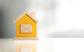 istock Yellow Toy House Made Of Wood With Mail Icon - Real Estate Concept 957859416