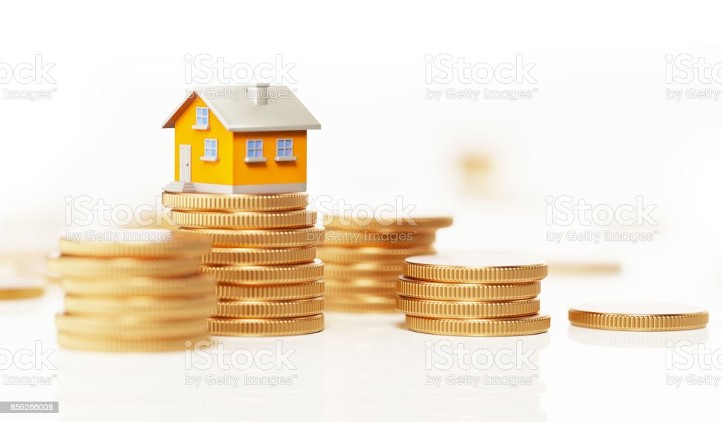 Yellow Toy House Sitting On Top Of Coin Stack: Real Estate and Savings Concept stock photo