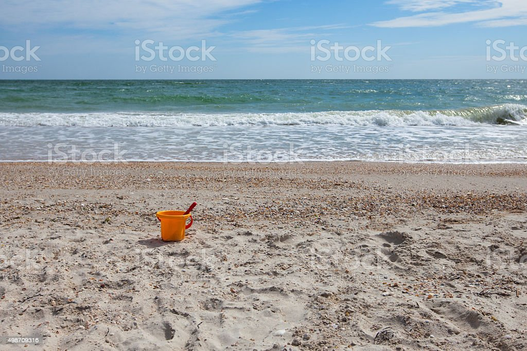 Yellow toy plastic bucket with a shovel on the beach stock photo