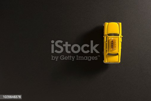 912120622 istock photo Yellow toy taxi car on a black background. 1025646376