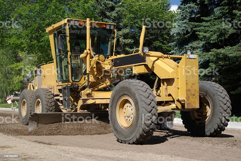 Yellow tractor over a dirt road next to green trees stock photo