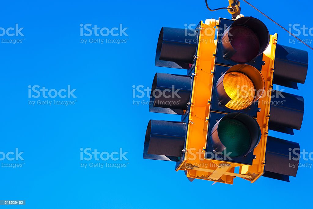 Yellow traffic light with a sky blue background stock photo