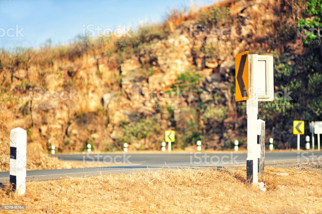 Yellow traffic sign 'Turn left' in the higth montain stock photo