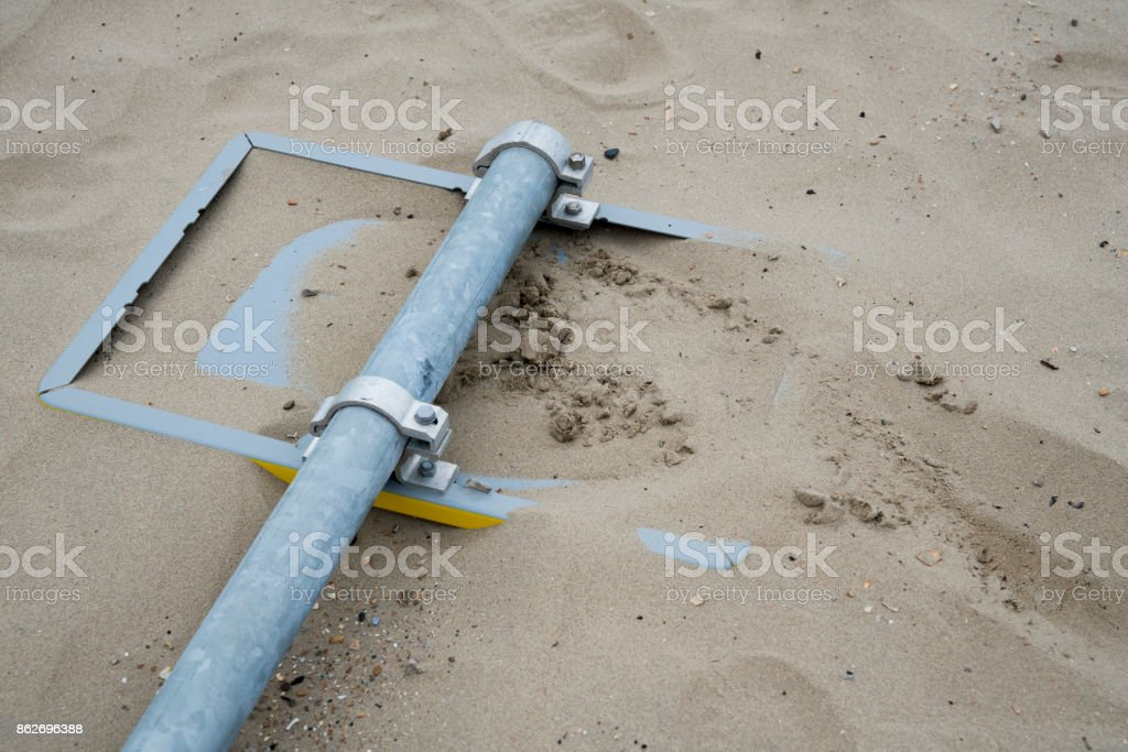 yellow traffic sign upside down in the sand, on the beach stock photo
