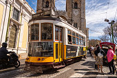 Lisbon, Portugal - 8 March 2020: Tourists riding the famous yellow Tram 28 in front of Lisbon Cathedral