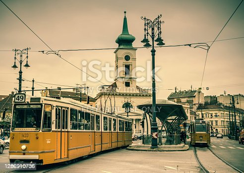 Yellow tram with boarded passengers leaving the station at Kalvin Square in Budapest on cloudy autumn day.