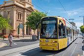Glenelg, Australia - November 13, 2017: Yellow tramway on the streets of Glenelg town