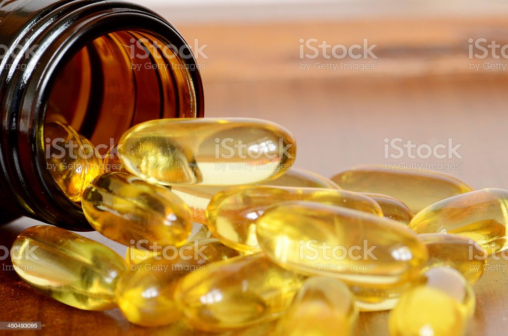 Yellow transparent capsules falling out of a brown bottle stock photo