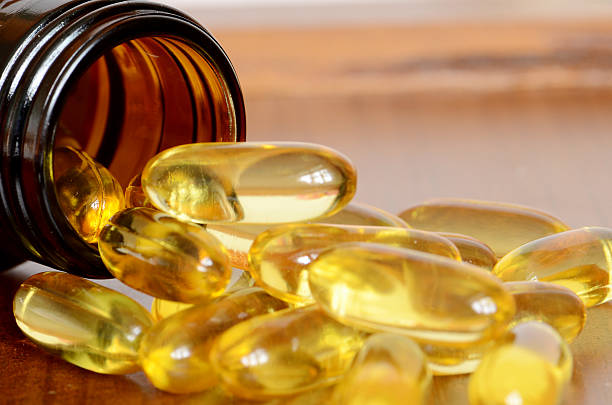 прозрачный желтый капсул. - vitamin d стоковые фото и изображения