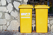 Two yellow plastic trash bins on the street