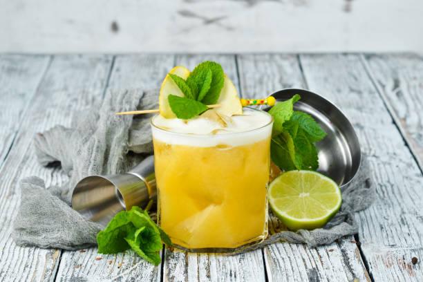 Cocktail tropical amarelo da bebida em um vidro. Maracujá, limão, rum. - foto de acervo