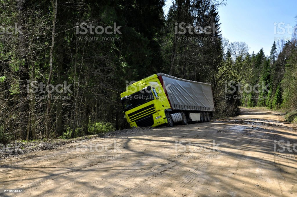 Yellow truck crashed to the forest road. stock photo