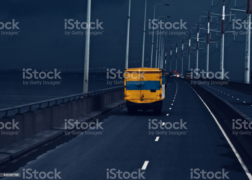 A yellow truck is running on a bridge with cloudy sky stock photo