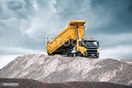 Delivery of sand to the construction site by yellow truck with raised body