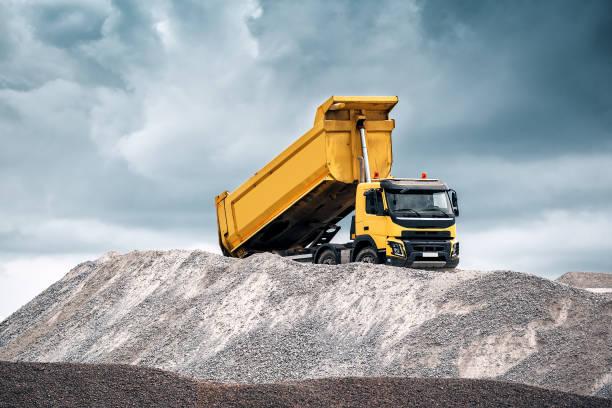 gele vrachtwagen met verhoogde lichaam - steengroeve stockfoto's en -beelden