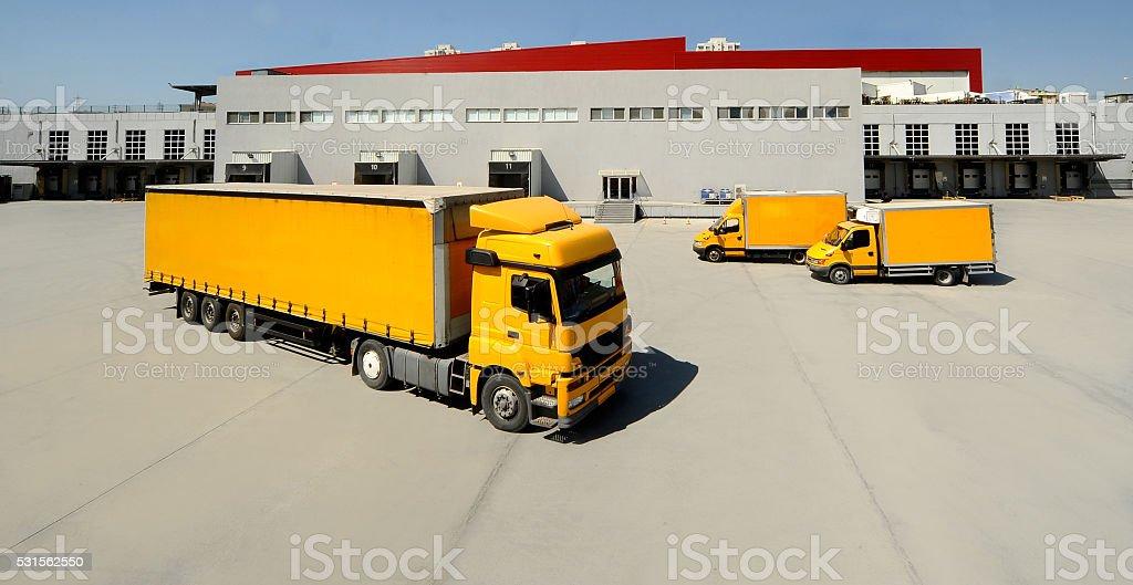 Yellow trucks at warehouse parking stock photo