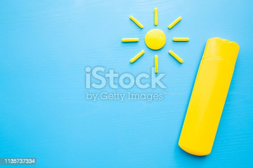 istock Yellow tube of sunscreen and sun shape on pastel blue background. Care about skin protection in hot summer. Sunbathing concept. Empty place for text, quote, sayings or logo. Top view. 1135737334