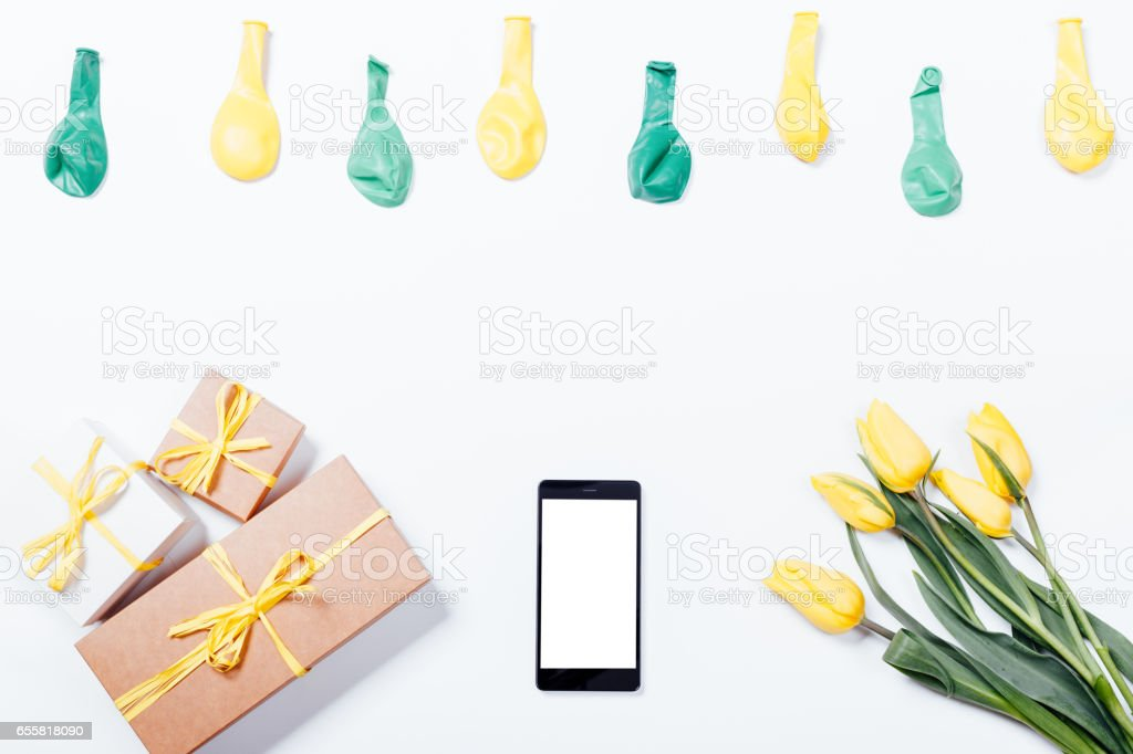 Yellow tulips, mobile phone, gift boxes with a ribbons and balloons on a white table stock photo