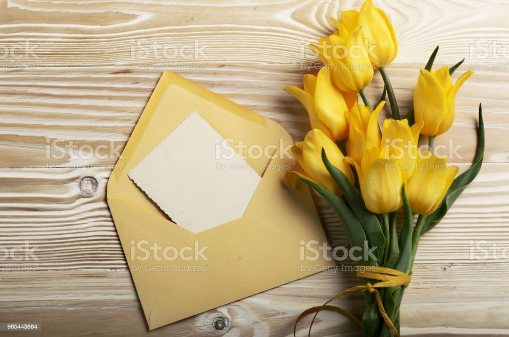 Yellow tulips near blank greeting card and envelope on natural wooden background with space for text zbiór zdjęć royalty-free