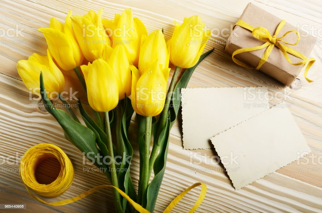 Yellow tulips near blank greeting card and gift box on natural wooden background with space for text - Zbiór zdjęć royalty-free (Bukiet)