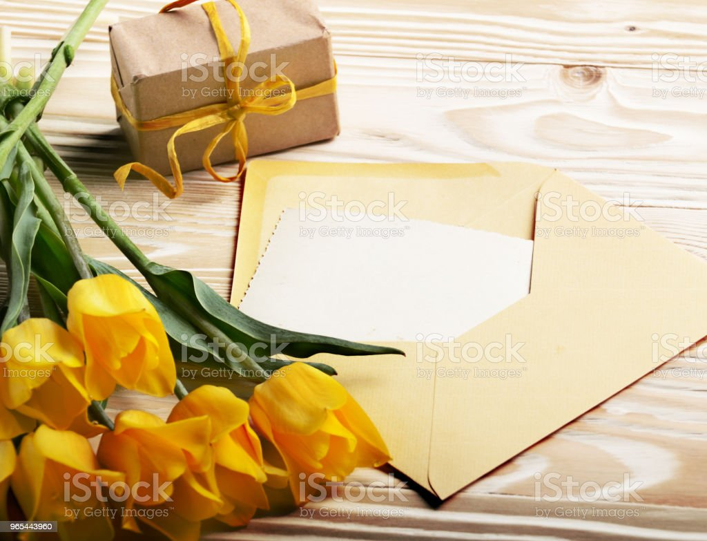 Yellow tulips near blank greeting card gift box and envelope on natural wooden background with space for text zbiór zdjęć royalty-free