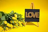 yellow tulips with love on blackboard