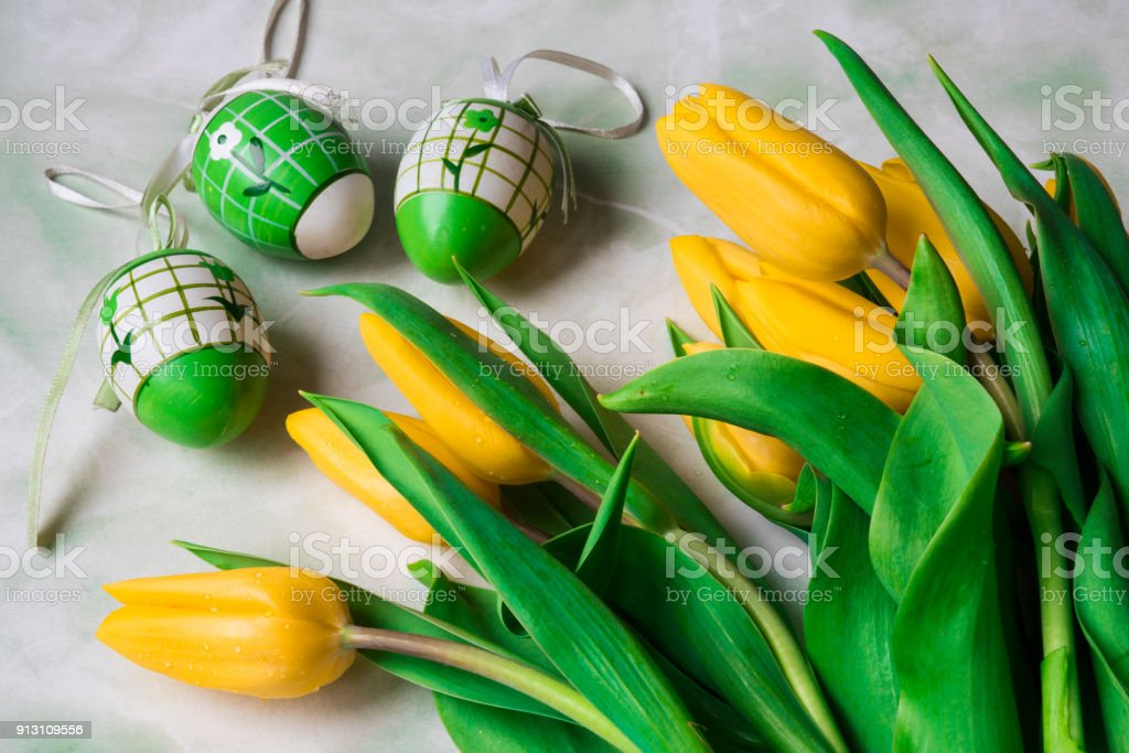 Yellow Tulips With Rain Drops And Plastic Easter Eggs Against Mint Green White Background
