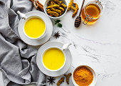 istock Yellow turmeric latte drink. Golden milk with cinnamon, turmeric, ginger  and honey over white marble background. 1278907627