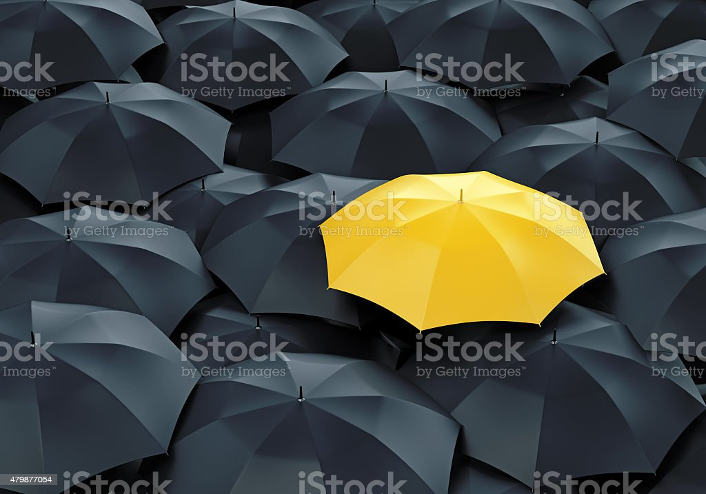 Yellow umbrella among dark ones stock photo