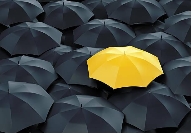 Yellow umbrella among dark ones stock photo