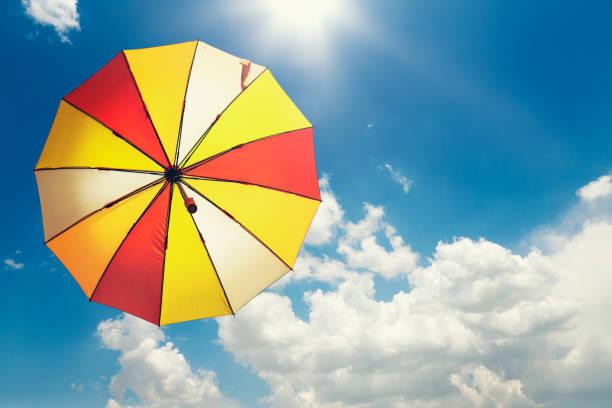 gelbe sonnenschirm am blauen himmel - wettervorhersage deutschland stock-fotos und bilder