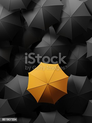 Yellow umbrella surrounded by black umbrellas is standing out from the crowd. Standing out from the crowd and individuality concept. Horizontal composition with copy space. Directly above.