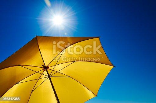istock Yellow Umbrella With Bright Sun And Blue Sky 936342386