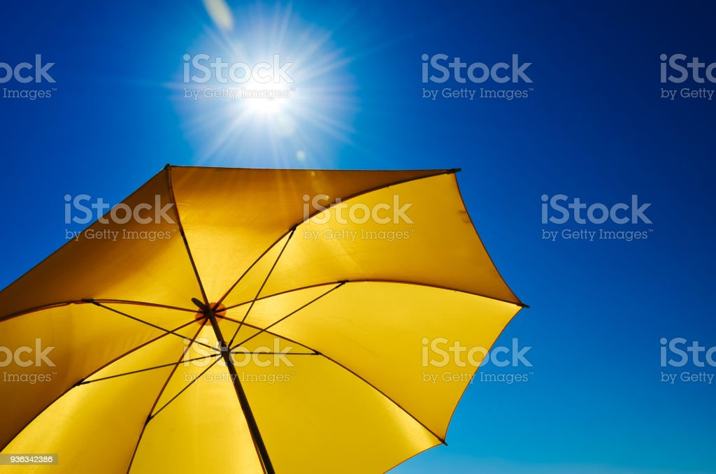 Yellow Umbrella With Bright Sun And Blue Sky stock photo