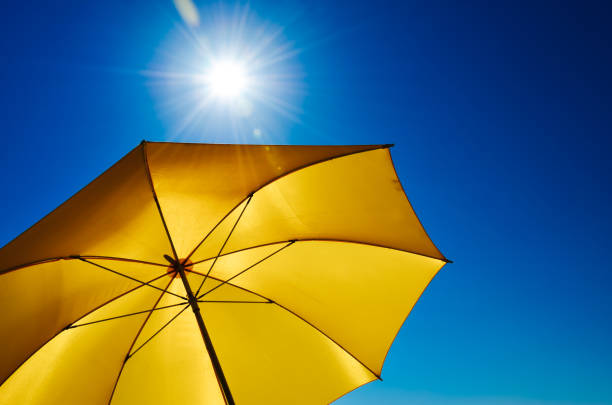yellow umbrella with bright sun and blue sky - protezione foto e immagini stock