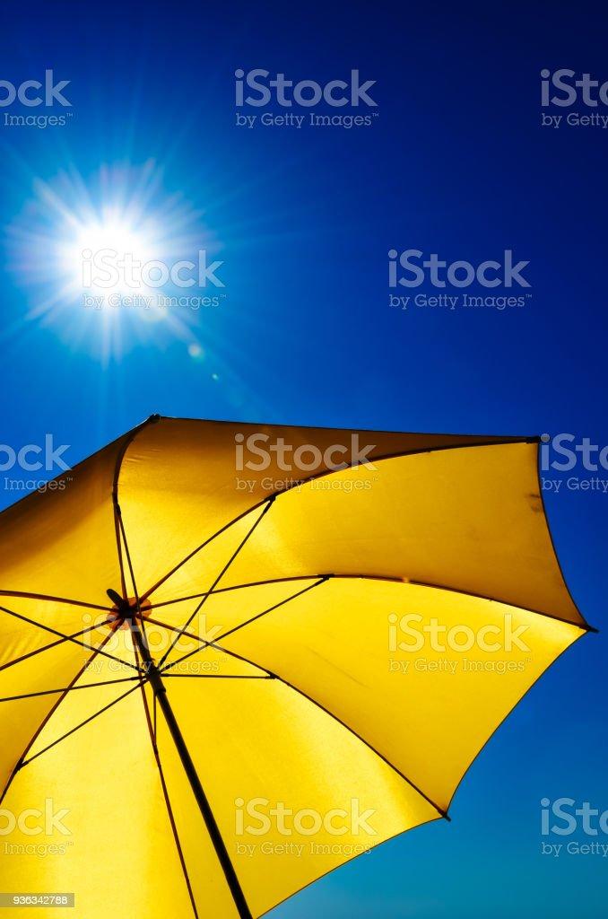 Yellow Umbrella With Bright Sun And Blue Sky stock photo