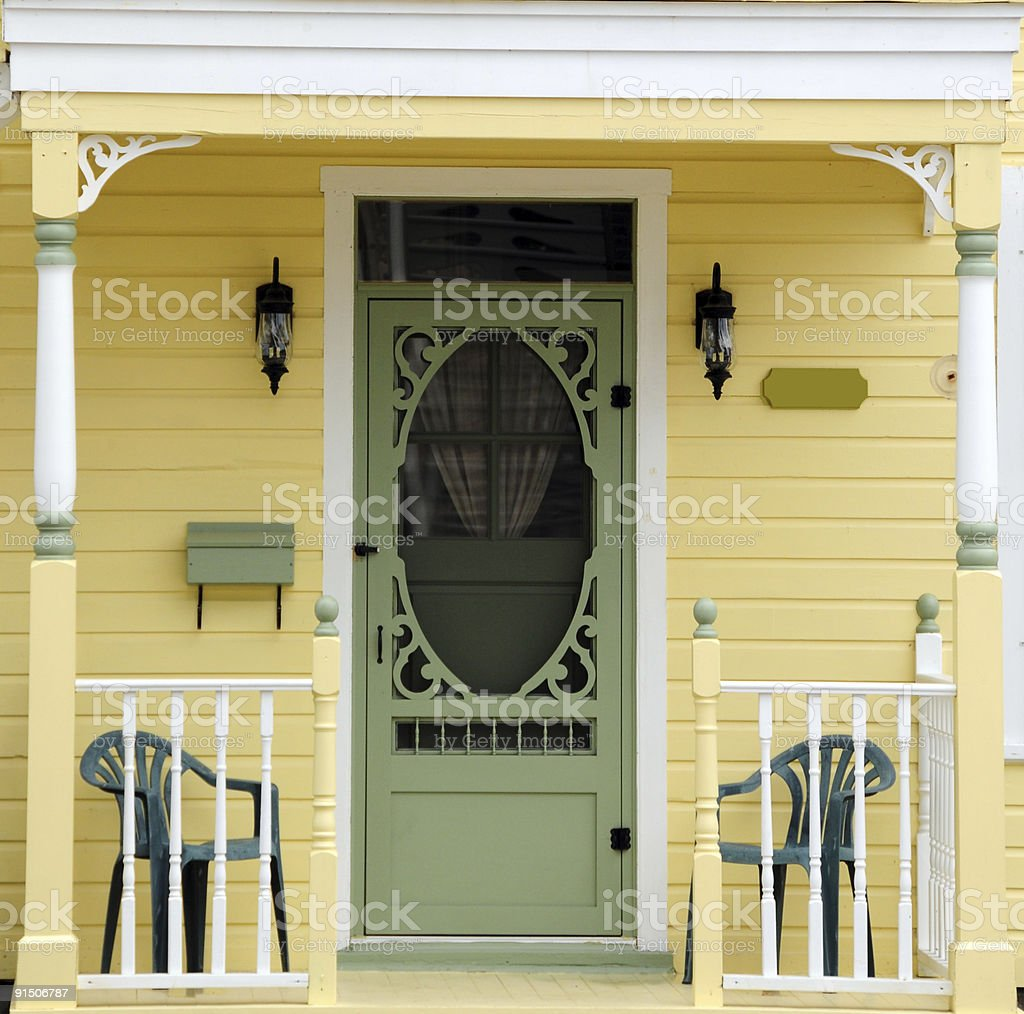 Yellow Victorian porch with green chairs and green door stock photo