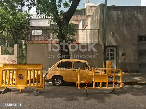 Buenos Aires, Argentina - October 27, 2019: Old vintage Fiat car model 600 in fairly good condition parked next to construction barriers. The city is so huge that at any given moment in some place something is being repaired
