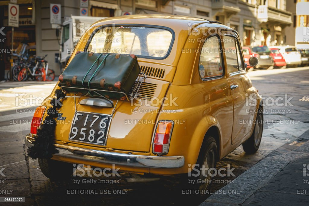 Yellow vintage Fiat 500 parked in the street in Florence (Italy).